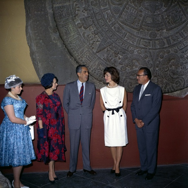 JFKWHP-KN-C22562. First Lady Jacqueline Kennedy stands in front of the Piedra del Sol (Aztec calendar, Sun Stone) during a visit to the Museo Nacional de Antropología (National Museum of Anthropology) of the Instituto Nacional de Antropología e Historia (National Institute of Anthropology and History) in Mexico City, Mexico. Left to right: Eva López Mateos; First Lady of Mexico, Eva Sámano de López Mateos; Subdirector of the Instituto Nacional de Antropología e Historia, Dr. Ignacio Bernal; Mrs. Kennedy; Director of the Instituto Nacional de Antropología e Historia, Dr. Eusebio Dávalos Hurtado. 29 June 1962.