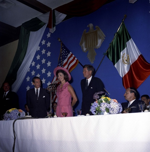 JFKWHP-KN-C22666-G. El presidente John F. Kennedy se encuentra con la primera dama Jacqueline Kennedy mientras ella daba un discurso en español en un almuerzo celebrado en honor al presidente de México, Adolfo López Mateos, y a la Primera Dama de México, Eva Sámano de López Mateos. En la mesa (L-R): el Presidente de la Comisión Permanente del Congreso de México, Rómulo Sánchez Mireles; El presidente López Mateos; La señora Kennedy; El presidente Kennedy; La señora López Mateos (en su mayoría oculta detrás de las flores); el Presidente de la Corte Suprema de México, Alfonso Guzmán Neyra. También en la foto está el intérprete del Departamento de Estado de los de Estados Unidos , Donald Barnes (en la parte trasera, detrás de la señora Kennedy). Hotel Maria Isabel, Ciudad de México, México, 30 de junio de 1962.