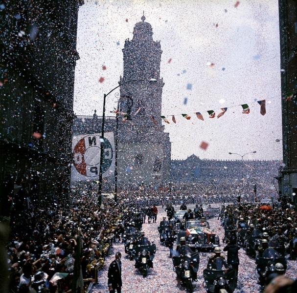 JFKWHP-ST-C1-27-62. El presidente John F. Kennedy se encuentra en un convertible durante el desfile de los automóviles a Los Pinos, la residencia oficial del Presidente de México, después de su llegada junto a la primera dama Jacqueline Kennedy en México. El presidente de México, Adolfo López Mateos (derecha), se encuentra en el coche con el presidente Kennedy. La Catedral de México y la Galería Palacio Nacional son visibles en el fondo. El Confeti cae en la caravana; los espectadores bordean la calle. Ciudad de México, México, 29 de junio de 1962.
