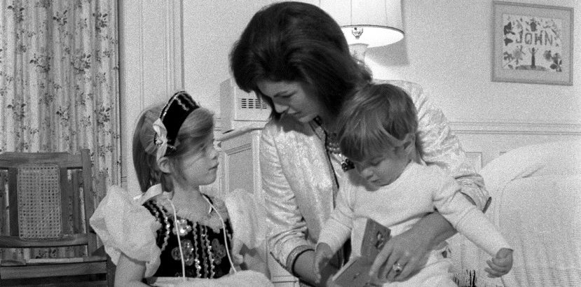 "ST-A28-13-62                           27 November 1962  First Lady Jacqueline Kennedy sits with her children Caroline and John, Jr.  Nursery, Mansion, White House, Washington, D.C.  Please credit ""Cecil Stoughton, White House/John F. Kennedy Presidential Library and Museum, Boston"""