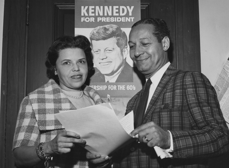 "PC1771 ca. 1960 Marjorie Lawson (left) stands with an unidentified man infront of a poster for John F. Kennedy's 1960 Presidential Campaign Please credit: ""Copyright Maurice Sorrell. President's Collection Photographs. John F. Kennedy Presidential Library and Museum, Boston"""