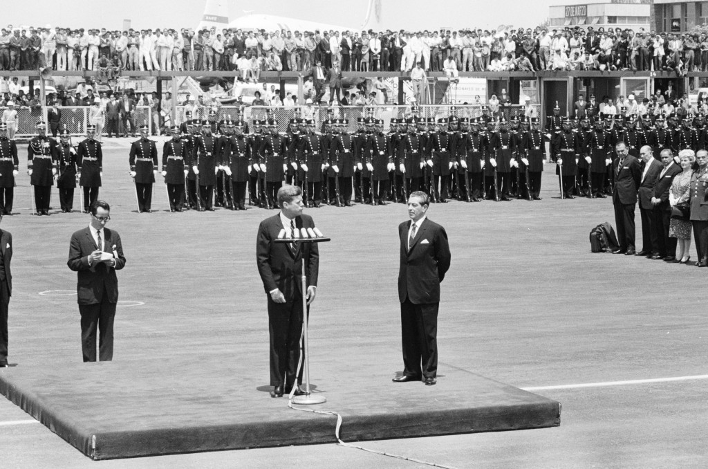 JFKWHP-KN-22522. President John F. Kennedy delivers remarks upon his arrival in Mexico City. President of Mexico, Adolfo López Mateos, stands on platform at right; U.S. State Department interpreter, Donald Barnes, stands below platform at left. Members of an honor guard stand in the background. Benito Juárez International Airport, Mexico City, Mexico, 29 June 1962.