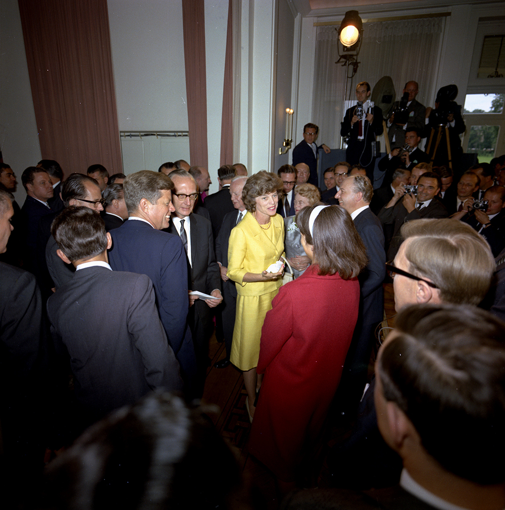 "KN-C29301 23 June 1963 President John F. Kennedy greets several officials during a meeting with Chancellor Konrad Adenauer. Photograph includes: President Kennedy, Eunice Shriver, President Heinrich Luebke, and a crowd of officials, guests, and photographers. Villa Hammerschmidt, Bonn, Germany. Please credit ""Robert Knudsen. White House Photographs. John F. Kennedy Presidential Library and Museum, Boston"""