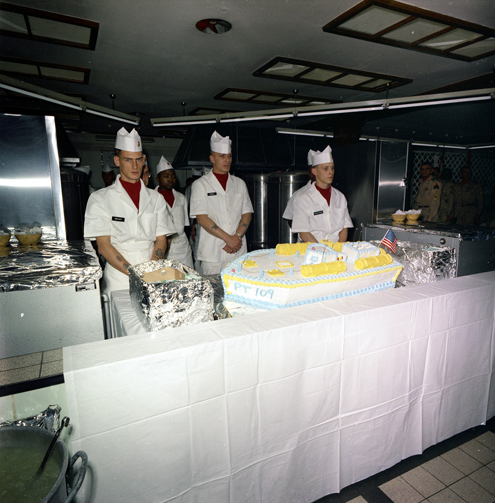 "KN-C29386 25 June 1963 PT-109 cake presented to President John F. Kennedy by unidentified Army Chefs. Troop Mess, Fliegerhorst Kaserne, Hanau, Germany. Please credit ""Robert Knudsen. White House Photographs. John F. Kennedy Presidential Library and Museum, Boston"""