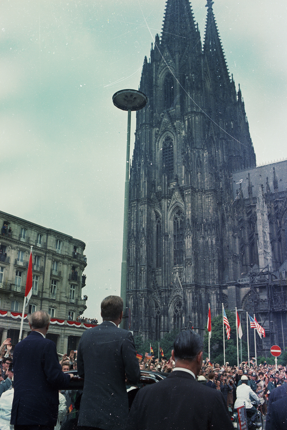 """ST-C230-33-63 23 June 1963 Trip to Europe: Germany, Cologne: Motorcade, Cathedral [Note: Scratches and blemishes throughout image are original to the negative.] Please credit """"Cecil Stoughton. White House Photographs. John F. Kennedy Presidential Library and Museum, Boston"""""""
